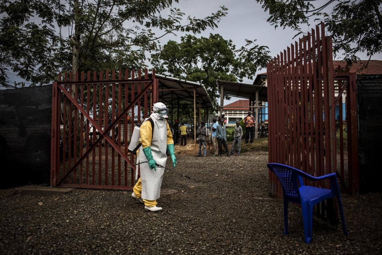 Un travailleur de santé MSF désinfecte l'entrée du centre d'isolement de Bunia après l'admission d'un patient affecté par Ebola. 2018. République démocratique du Congo.  © John Wessels