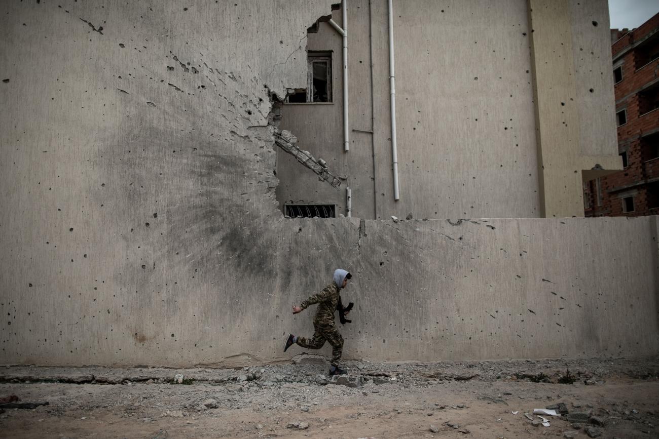 Un combattant du gouvernement d'union nationale (GNA) se met à l'abri des tirs des snipers de l'Armée nationale libyenne (ANL) sur une ligne de front à Tripoli, le 17 février 2020. Ce jour là est symbolique. Il marque la date anniversaire de la révolution de 2011 qui a fait chuter le Guide Mouammar Kadhafi et mis fin à son régime. Depuis, la Libye, divisée en territoires rivaux avec plusieurs gouvernements se disputant le pouvoir et le contrôle de ses ressources, reste marquée par des épisodes de violents combats.Tripoli. 17 février 2020. ©Amru Salahuddien.  © Amru Salahuddien