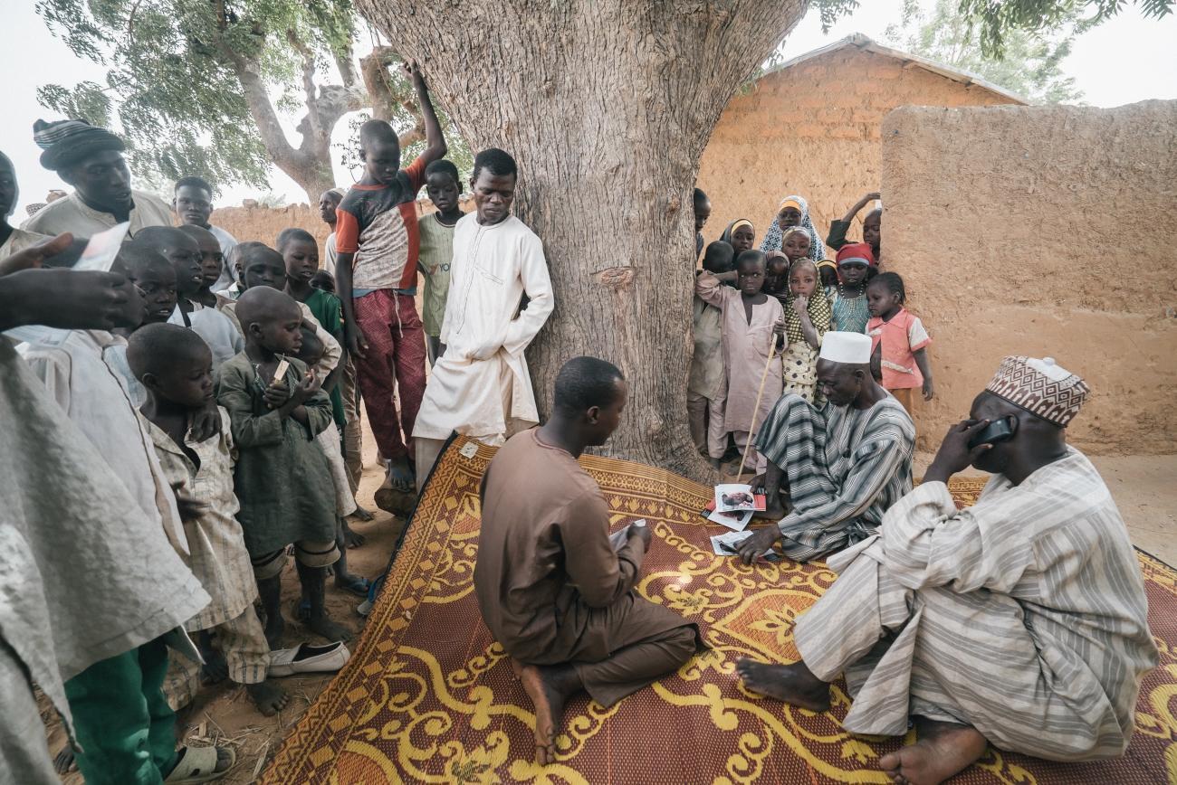 L'équipe de sensibilisation de l'hôpital de Sokoto a commencé à rechercher activement des cas dans l'État de Sokoto en janvier 2017. Ici, dans un village du gouvernement local de Dange-Shuni, l'équipe montre des brochures à la communauté locale pour vérifier s'il y a des personnes infectées par la maladie dans la région. Ils informent également les gens sur les causes du noma et sur l'importance d'un traitement dès les premiers stades de la maladie.  © Claire Jeantet - Fabrice Caterini/INEDIZ