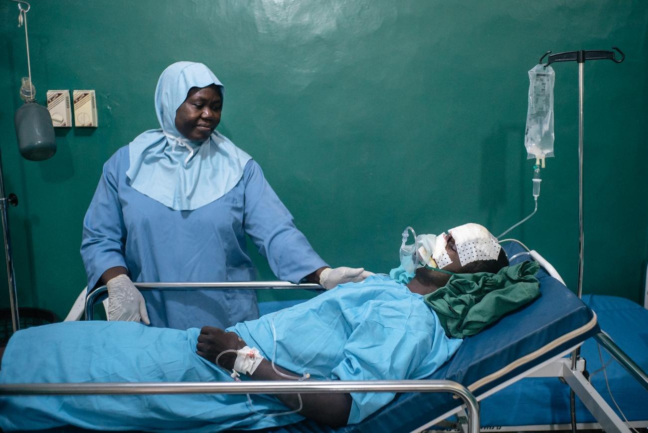 Bilya, 20 ans, un patient atteint de noma, se repose dans la salle de réveil de l'hôpital de Sokoto, après sa première intervention chirurgicale. Lady Bello, infirmière, prend soin de lui. Le personnel s'assure que les patients se rétablissent rapidement et évitent les infections. Quatre fois par an, une équipe de chirurgiens plastiques et maxillo-faciaux, d'anesthésistes et d'infirmières vient à l'hôpital de Sokoto.  © Claire Jeantet - Fabrice Caterini/Inediz