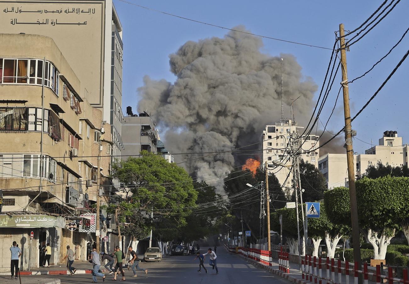 Des Palestiniens fuient le quartier de la tour Al-Sharouk, bombardée par l'armée israélienne. Ville de Gaza, le 12 mai 2021.  © Mohammed Abed/AFP