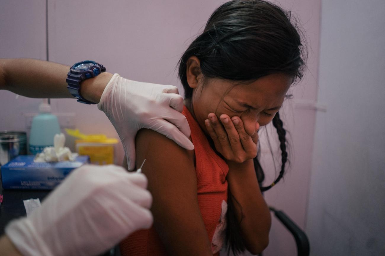 Une jeune fille du quartier de Tondo, à Manille, est vaccinée contre le HPV dans un dispensaire de l'ONG Likhaan, partenaire de MSF. Likhaan fournit des services de soins de santé en matière de reproduction aux familles à faible revenu aux Philippines, où il existe encore un écart dans la sensibilisation des femmes à leurs droits en matière de procréation.  © Hannah Reyes Morales