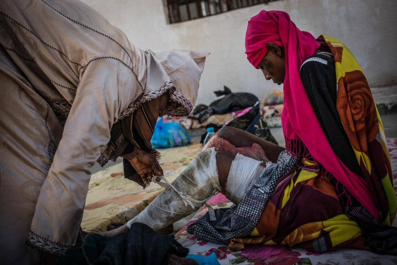 Une femme brûlée aux jambes reçoit de l'aide d'une autre détenue dans le camp de Sorman.  © Guillaume Binet/Myop