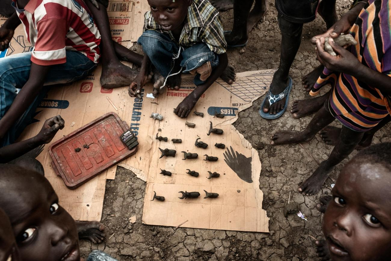 Des enfants fabriquent des figurines de bétail en boue. Près de 40 % de la population du camp de protection des civils est âgée de moins de cinq ans.  © Peter Bauza