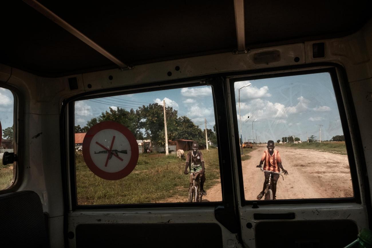 Deux enfants font du vélo derrière un véhicule MSF. La ville de Bentiu, autrefois un important centreadministratif, politique et économique, est aujourd'hui en ruine.  © Peter Bauza