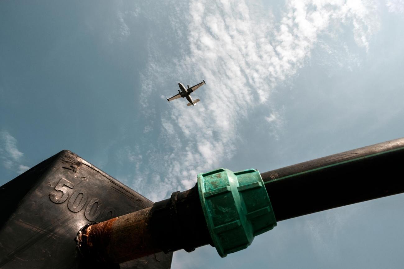 Un avion survole un réservoir d'eau du camp de protection des civils. Les maladies causées par les mauvaises conditions d'approvisionnement en eau et d'assainissement sont fréquentes dans le camp.  © Peter Bauza