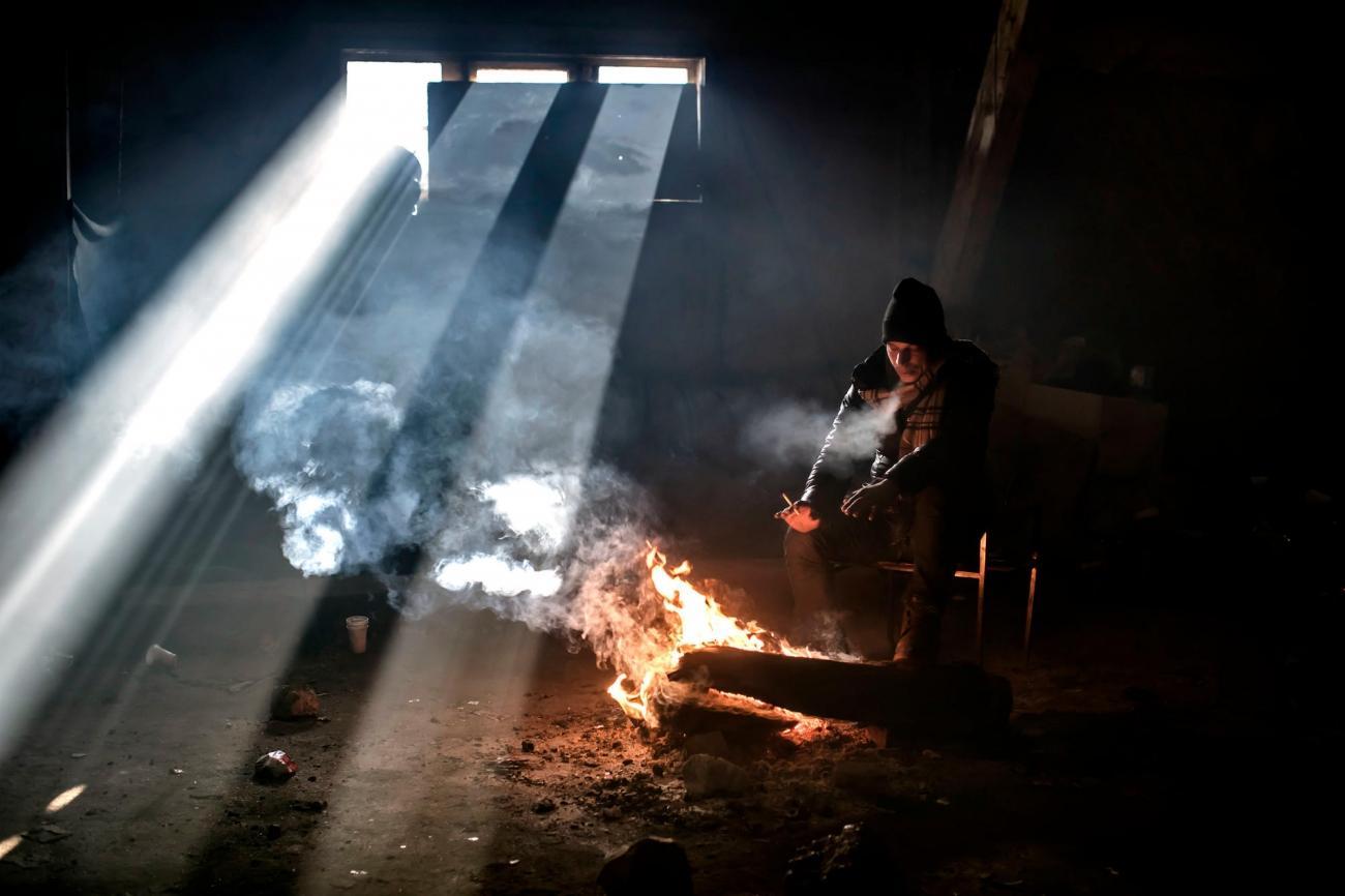 Un homme tente de se réchauffer dans un squat deBelgrade. L'hiver la température peut descendre jusqu'à- 20°C. Serbie. 2017.  © Paul Hansen/Dagens Nyheter