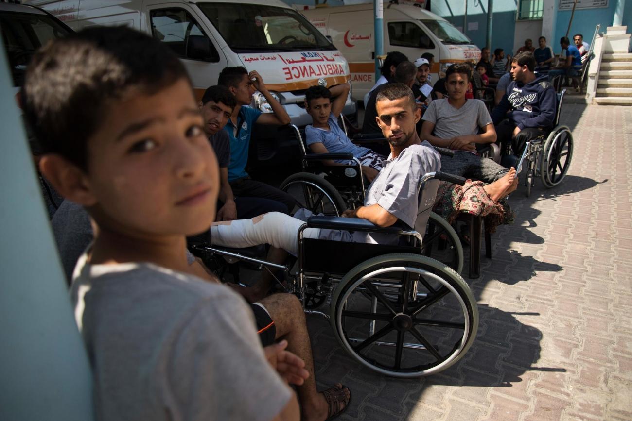 File d'attente dans la clinique de Beit Lahia. Des patients tentent de se mettre à l'ombre sur le parking de l'ambulance. Bande de Gaza. 2018.  © Aurelie Baumel/MSF