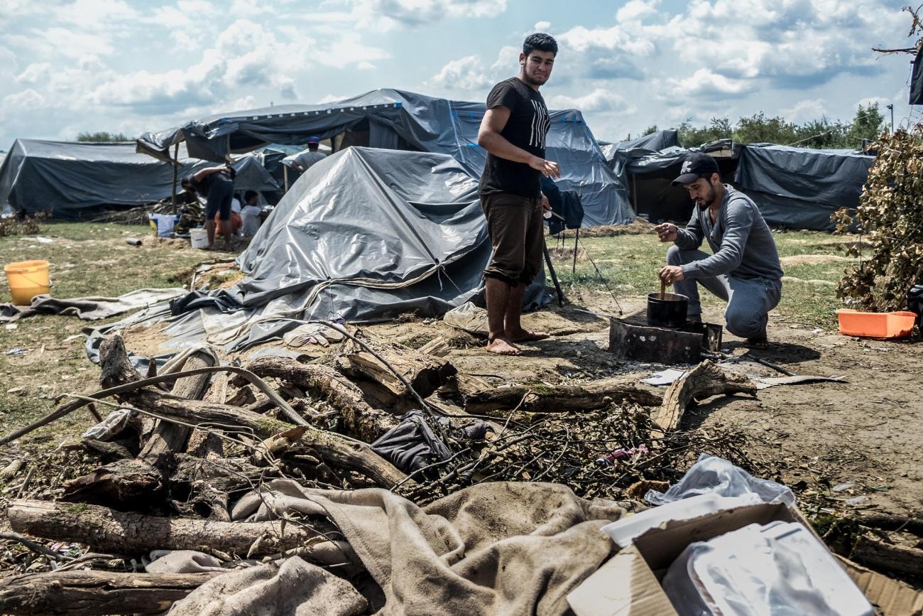 Deux hommes originaires de Syrie cuisinent avec des matériaux de récupération dans uncampinformel près de Velika Kladuša. Bosnie-Herzégovine. 2018.  © Kamila Stepien