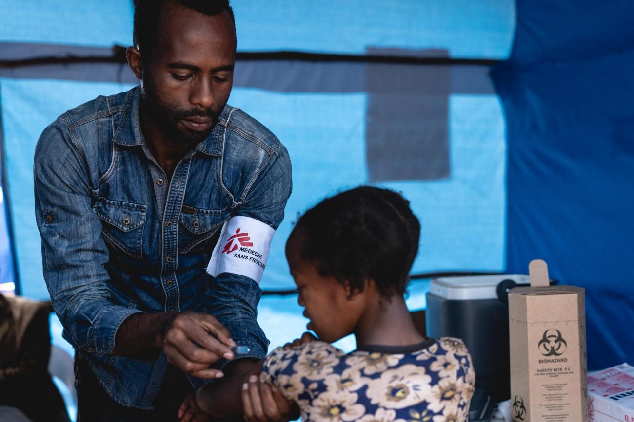 Un volontaire MSF vaccine un enfant contre la rougeole dans le cadre d'une campagne de vaccination de masse organisée par les autorités éthiopiennes.Éthiopie. 2018.  © Gabriele François Casini/MSF