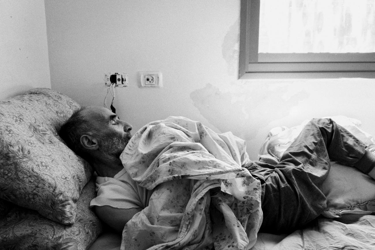 Mahmoud est un Palestinien de 74 ans qui souffre de troubles cognitifs dus à un accident vasculaire cérébral. Il a par la suite été frappé par des soldats israéliens à un check-point. Il est désormais alité et pris en charge par sa femme. Palestine. 2018.  © Moises Saman/Magnum Photos