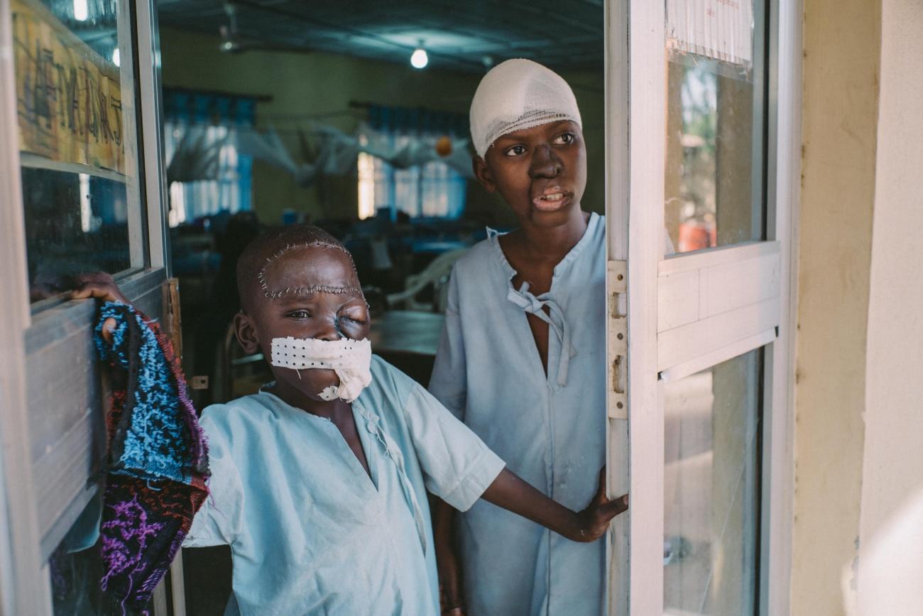 Umar a 8 ans et il vient de l'État de Kano. Il se tient à l'entrée de l'unité de soins post-opératoires de l'hôpital de Sokot, avec un autre patient âgé de 15 ans. Nigeria. 2017.  © Claire Jeantet - Fabrice Caterini/INEDIZ