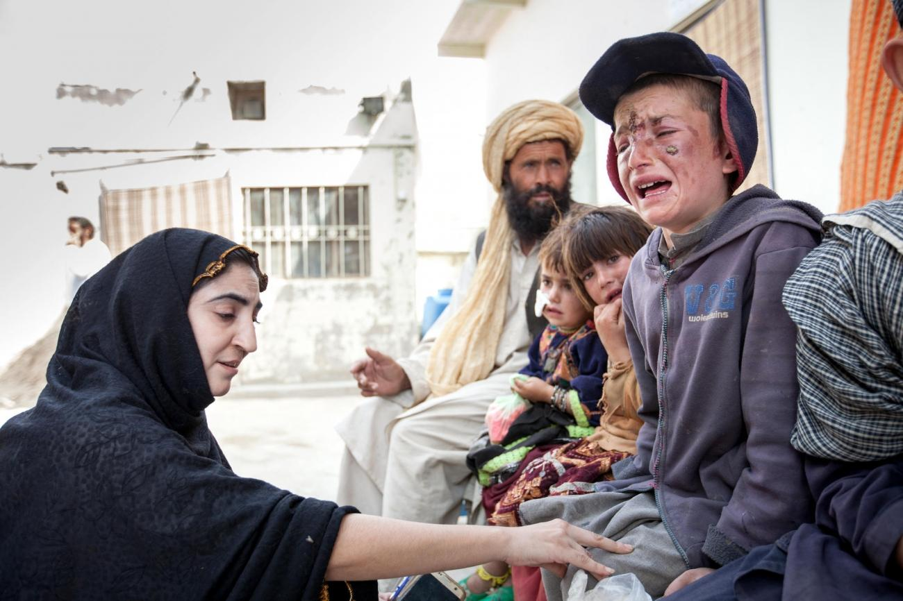 Une conseillère MSF rassure un jeune garçon avant qu'il reçoive son traitement contre la leishmaniose cutanée dans la clinique de Kuchlak. Pakistan. 2018.  © Khaula Jamil