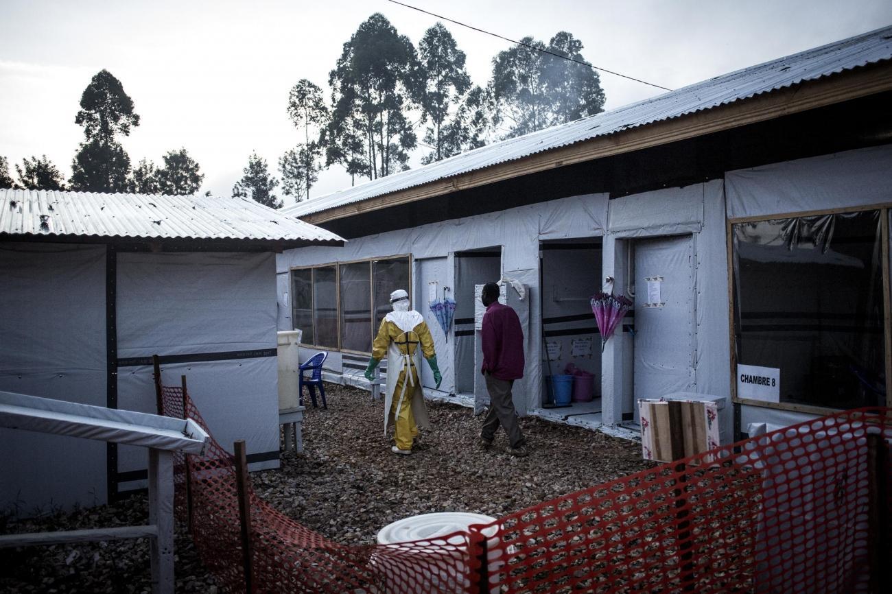 Un travailleur de santé MSF accompagne un homme susceptible d'être atteint par Ebola. Centre de traitement Ebola de Butembo. République démocratique du Congo. 2018.  © John Wessels