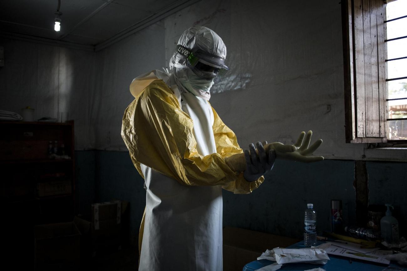 Un travailleur de santé MSF revêt son équipement de protection personnel avant d'entrer dans la zone à risque du centre d'isolement Ebola de Bunia. Il va procéder à une évaluation de l'état des patients. Novembre 2018. République démocratique du Congo.  © John Wessels