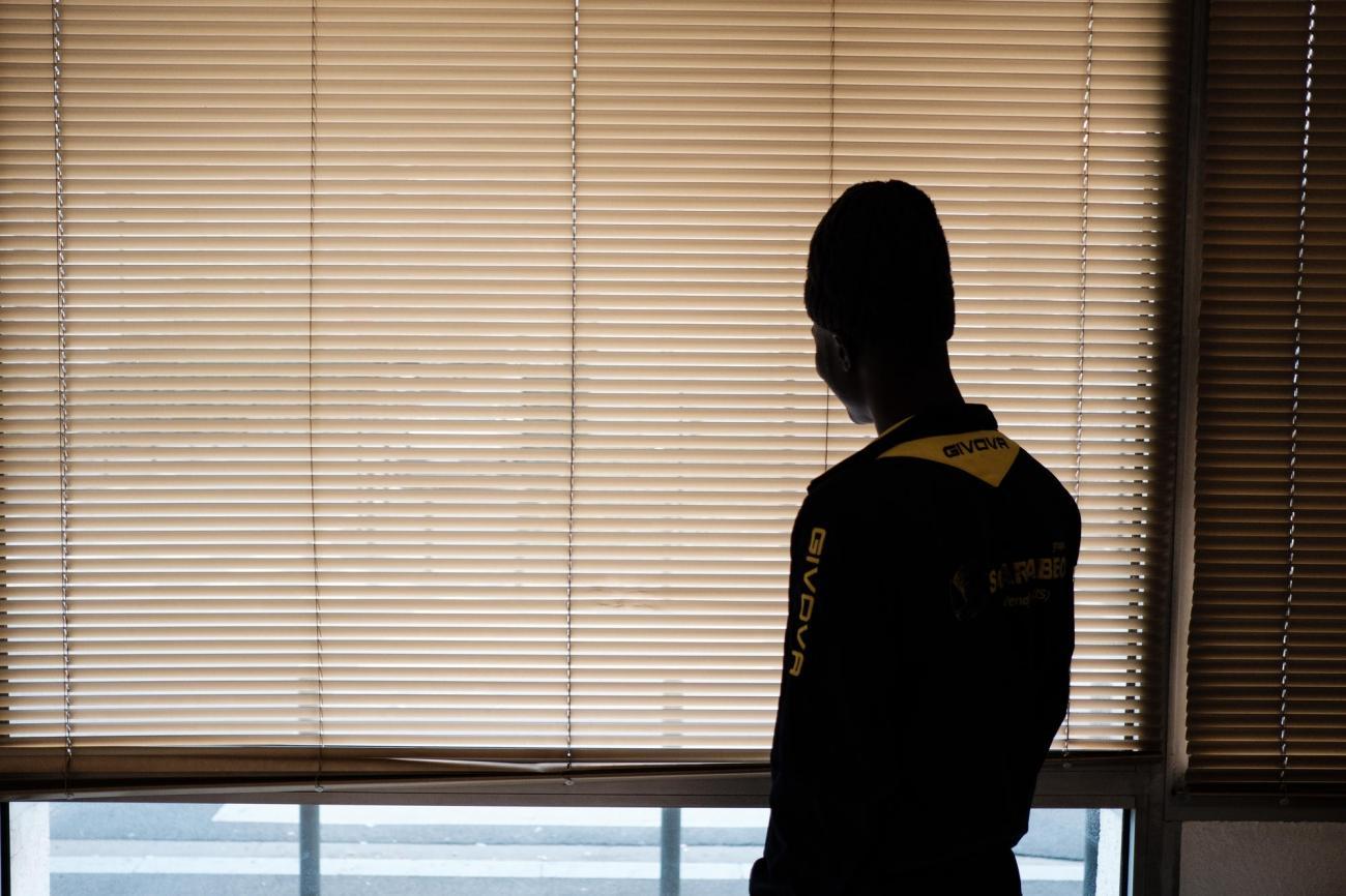 Un jeune regarde par la fenêtre dans le hall d'entrée de l'hôtel.  © Augustin Le Gall/Haytham