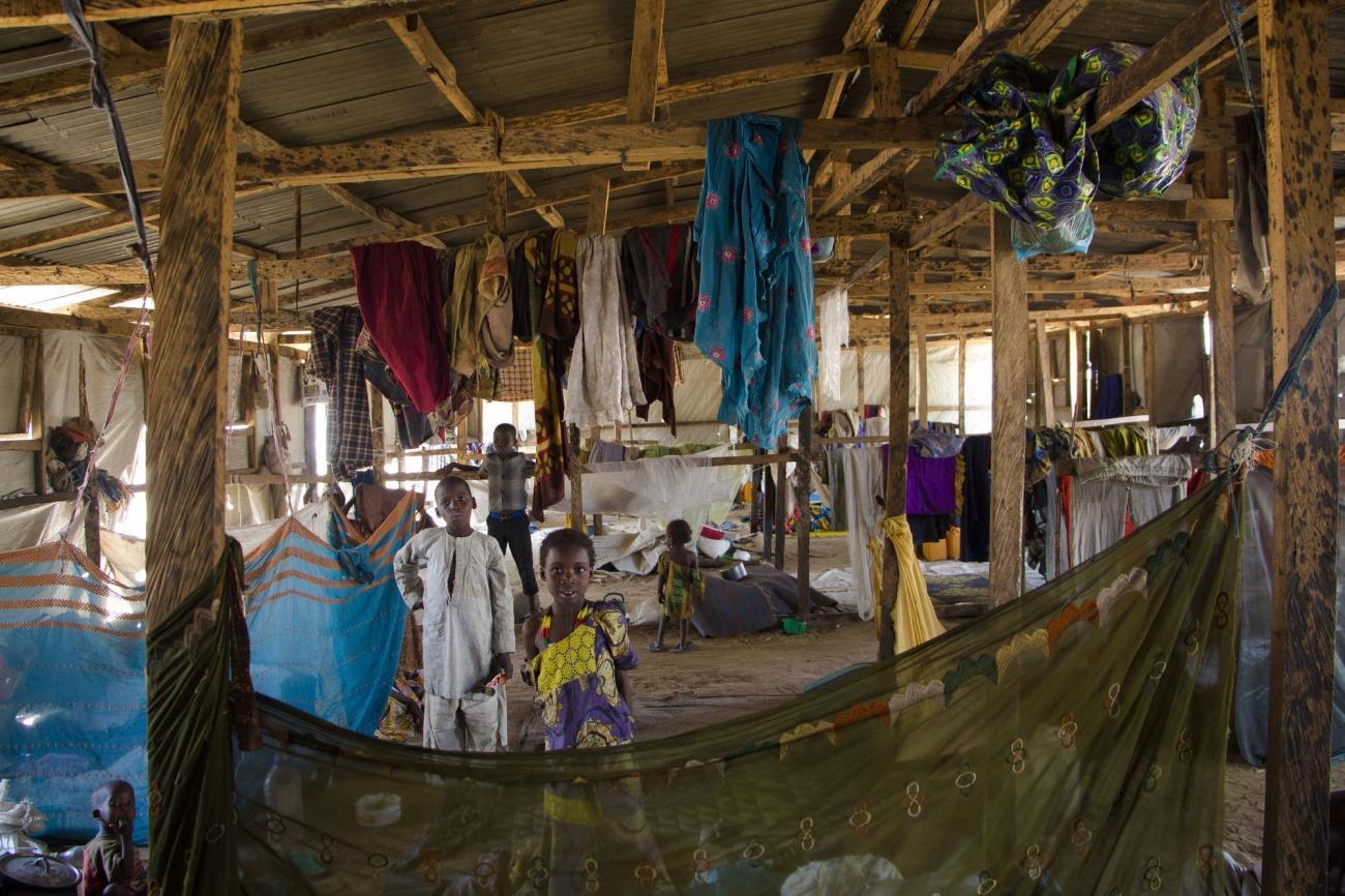 Des enfants dans un abri collectif. 60 à 70 personnes peuvent vivre dans ce type d'abri avant de se voir attribuer un abri personnel pour eux et leur famille. Ils peuvent cependant habiter pendant des mois dans un abri collectif. Bama. Nigeria. 2018.  © Natacha Buhler/MSF