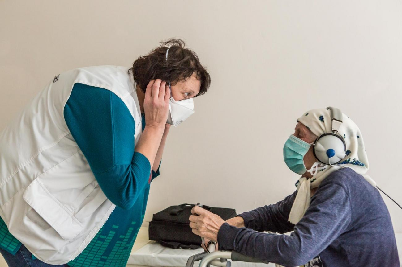 Olena est une infirmière MSF. Elle effectue des tests d'audition sur une patiente. Elle s'appelle Lidjia et a 78 ans. Ukraine. 2018.  © Oksana Parafeniuk