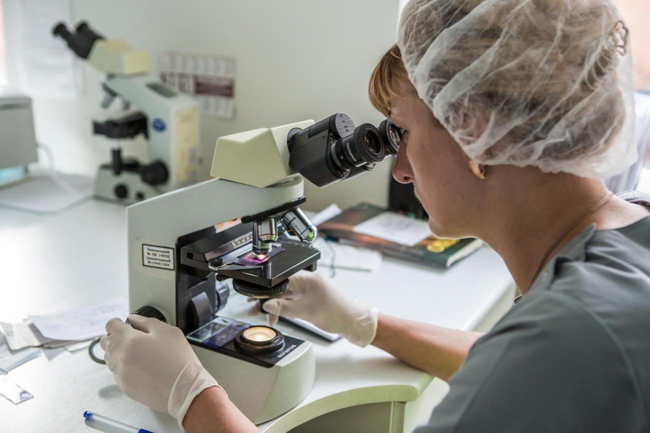 Une biologiste étude un prélèvement au microscope. Ukraine. 2018.  © Oksana Parafeniuk