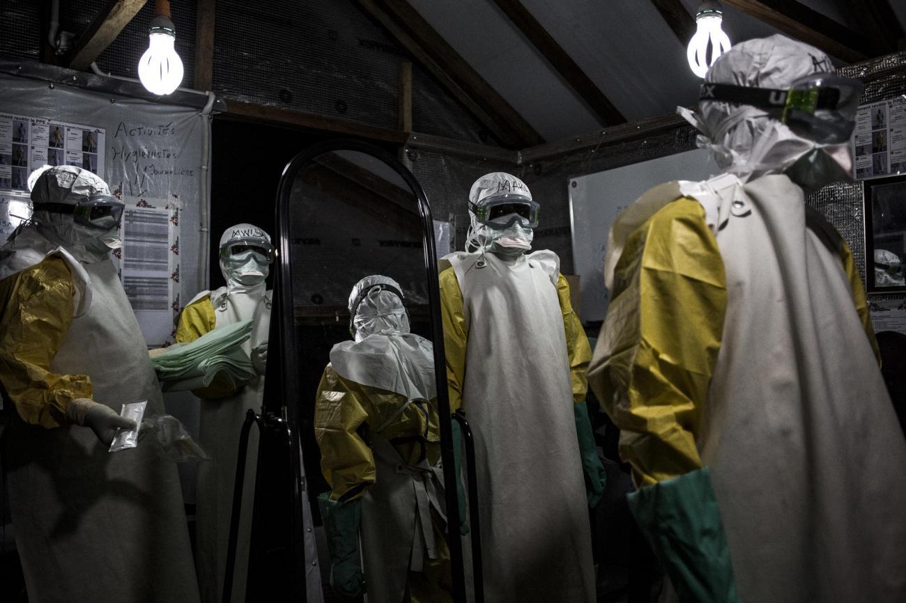 Des travailleurs de santé MSF revêtent leur équipement de protection personnel avant d'entrer dans la zone à risque du centre de traitement Ebola de Butembo. Il vont procéder à une évaluation de l'état des patients. Novembre 2018. République démocratique du Congo.  © John Wessels
