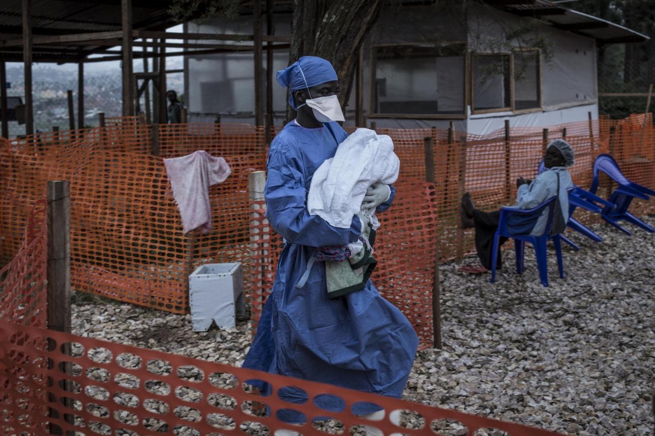 Un ancien patient Ebola aujourd'hui guéri est en train de transporter un nourrisson de 4 jours possiblement atteint par la maladie. Une fois guéris les patients Ebola sont immunisés contre la maladie et ont la possibilité de travailler à l'intérieur des zones à risque des centres de traitement. Butembo. Novembre 2018. République démocratique du Congo.  © John Wessels