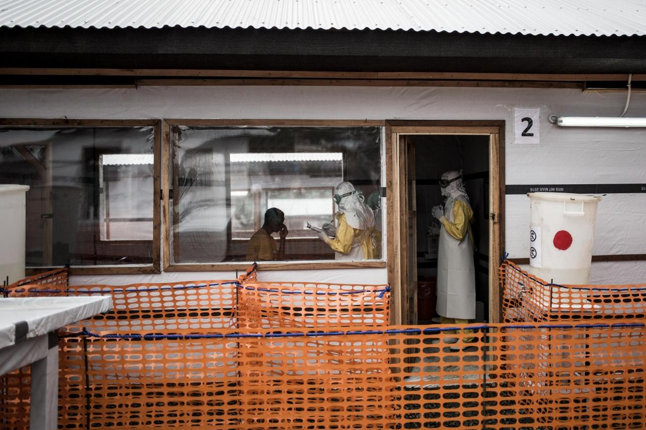 Des travailleurs de santé MSF réalisent l'évaluation médicale d'un patient possiblement affecté par Ebola. Ils sont à l'intérieur du centre d'isolement Ebola de Bunia. Novembre 2018. République démocratique du Congo.  © John Wessels