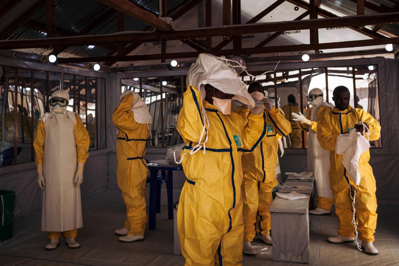 Des travailleurs de santé MSF revêtent leur équipement de protection individuel avant d'entrer dans la zone à risque du centre de traitement Ebola. République démocratique du Congo. 2018.  © Alexis Huguet