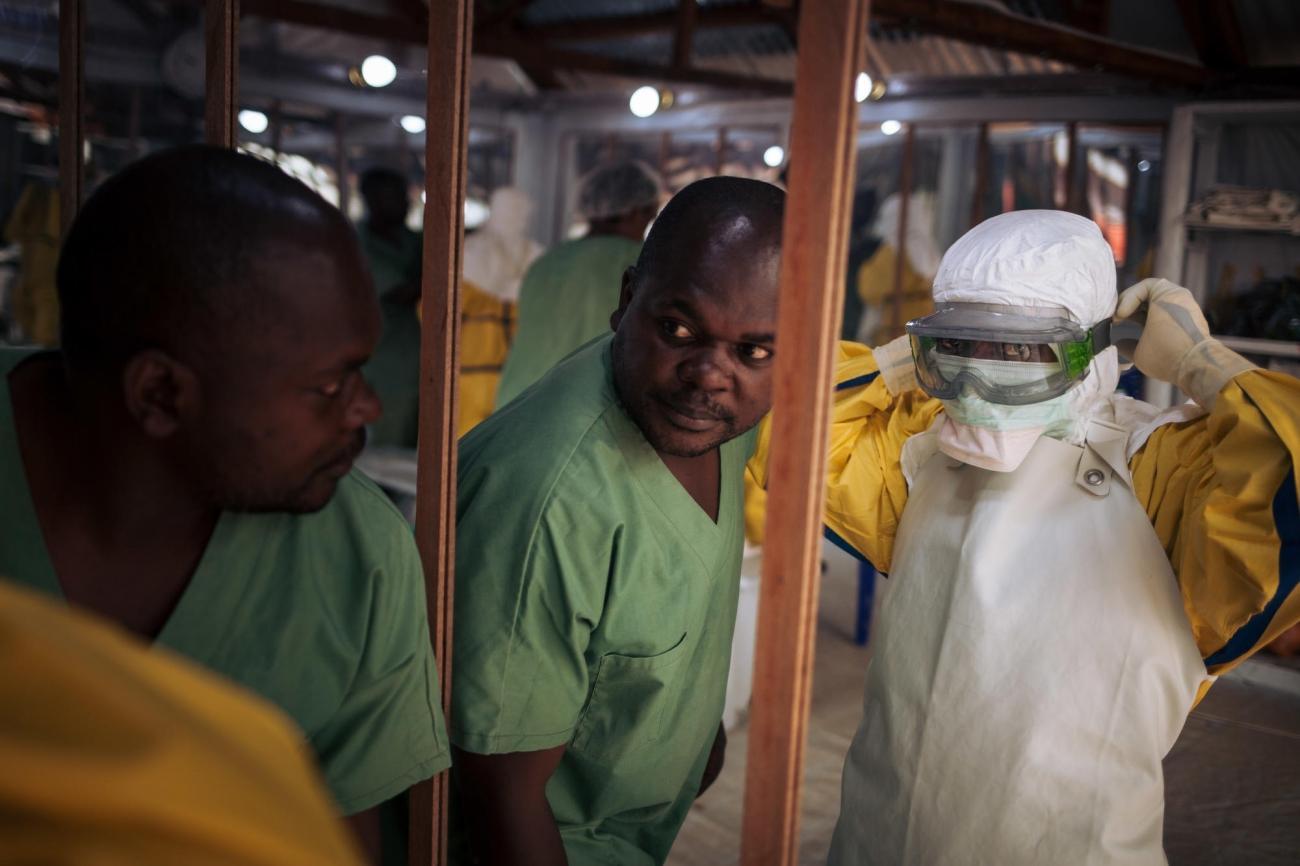 Un travailleur de santé revêt son masque avant d'entrer dans la zone à risque d'un centre de traitement Ebola. Novembre 2018. République démocratique du Congo.  © Alexis Huguet