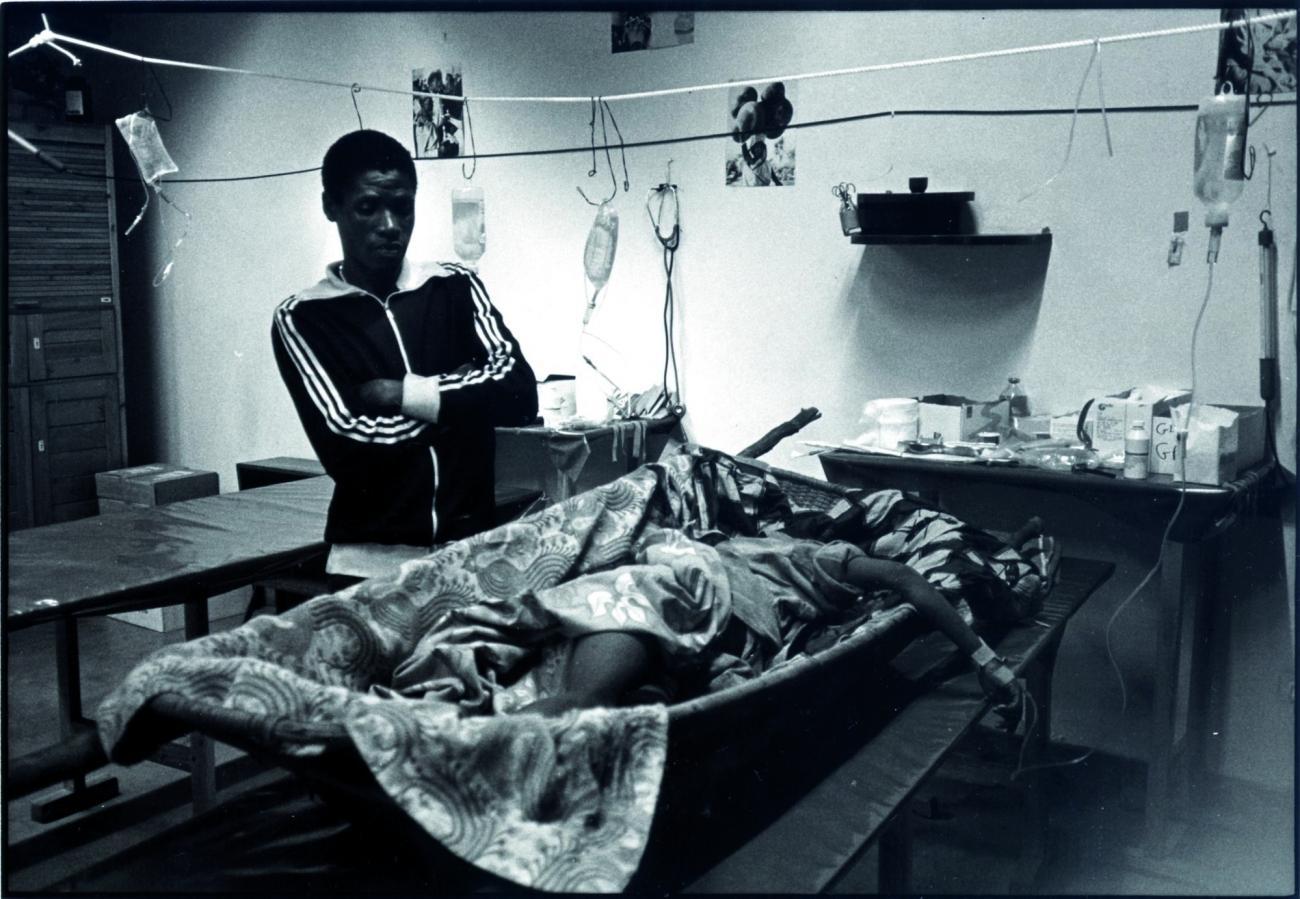 Un patient et son frère à l'hôpital MSF-CICR de Kigali. Malgré des discussions intenses avec les équipes de MSF, le colonel en charge de la zone n'a pas toléré la présence de cet accompagnant dans l'hôpital. Obligé de quitter les lieux, il se fait tuer 100 mètres plus loin. Avril 1994. Rwanda.  © Xavier Lassalle/MSF