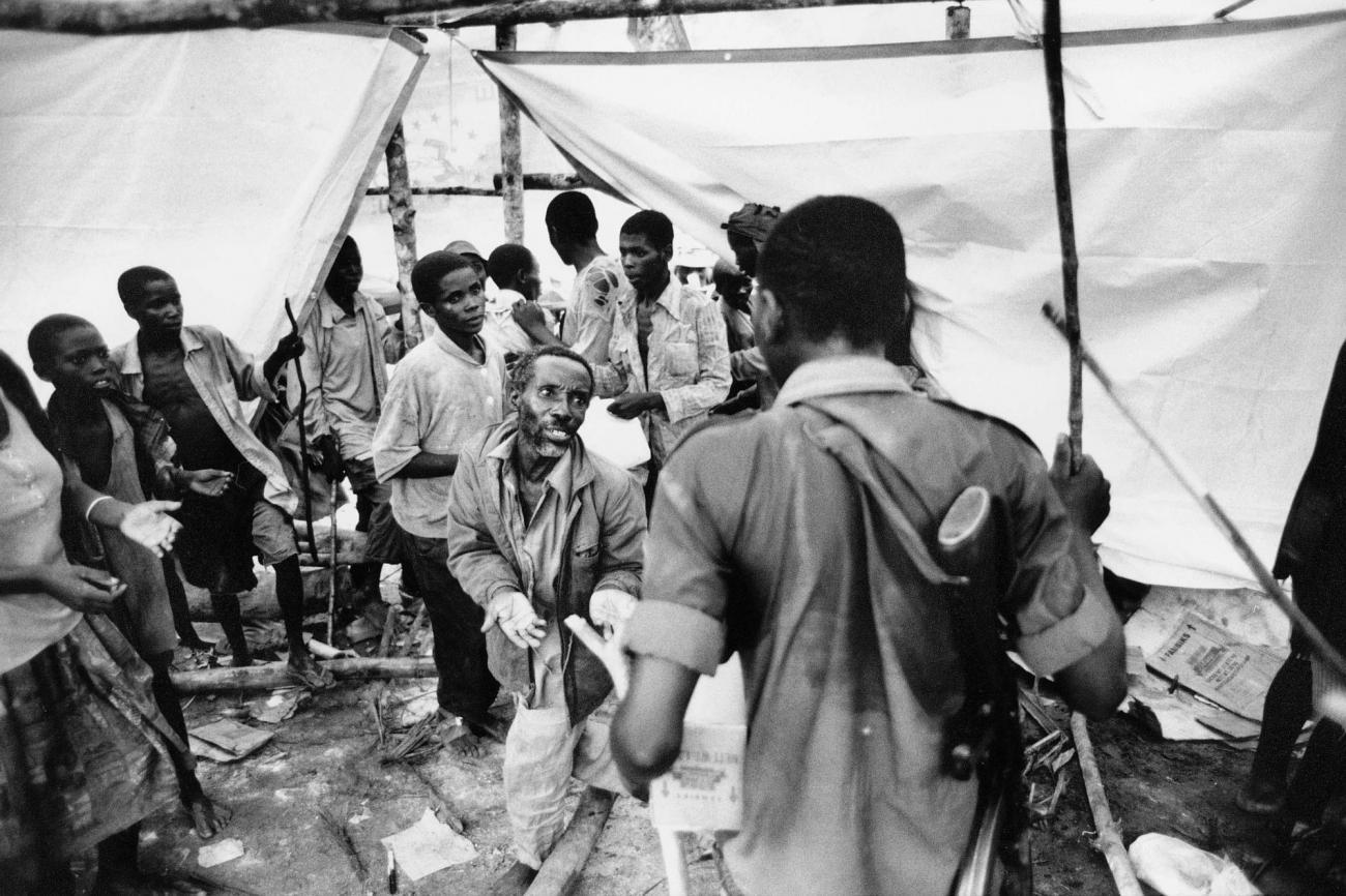 Réfugiés rwandais hutus au Zaïre. Désespérés, certainscommencent à piller les stocks alimentaires du Programme alimentaire mondial. Des soldats rebelles tentent de mettre fin au pillage. 1997.  © Kadir Van Lohuizen/Noor