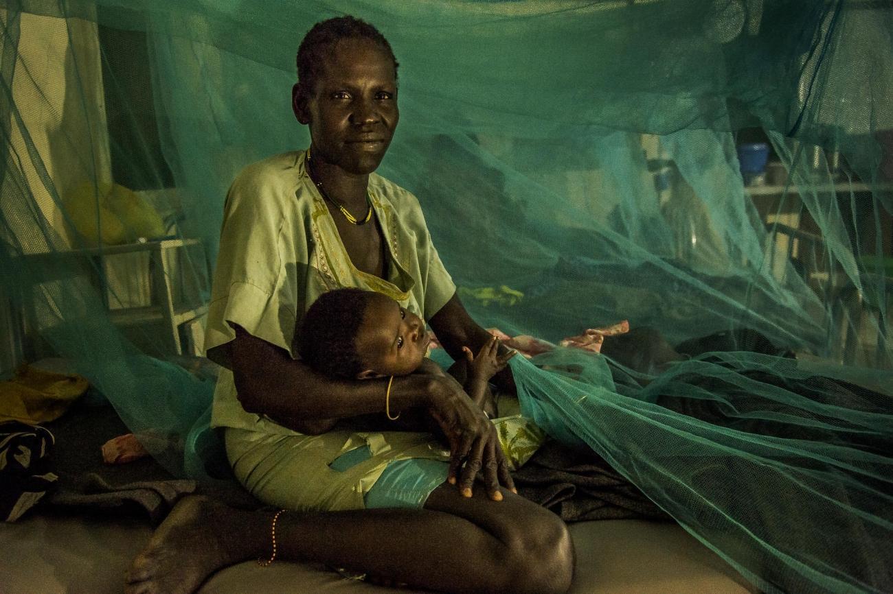 La nuit tombe sur le service pédiatrique de l'hôpital d'Old Fangak. Les moustiquaires ont été étendues autour des lits pour protéger des moustiques et du paludisme. Une patiente berce son enfant. 2017. Soudan du Sud.  © Frederic NOY/COSMOS