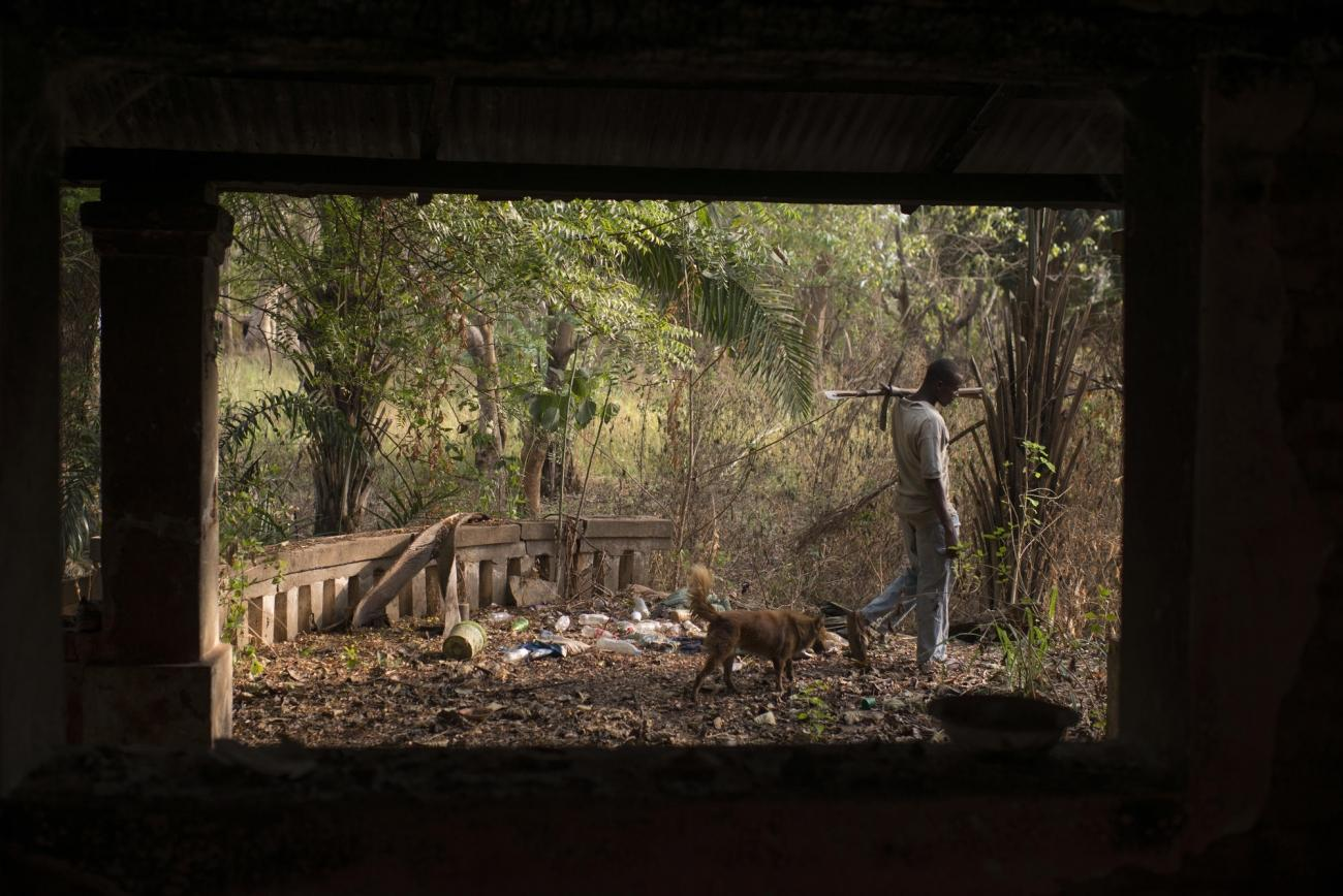 Un homme marche près d'une villa abandonnée.  © Colin Delfosse/Ouf of Focus