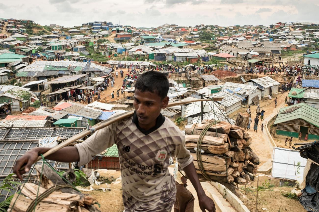 Un homme transporte du bois dans l'un des camps de réfugiés du district deCox's Bazar, au Bangladesh.  © Robin Hammond/NOOR