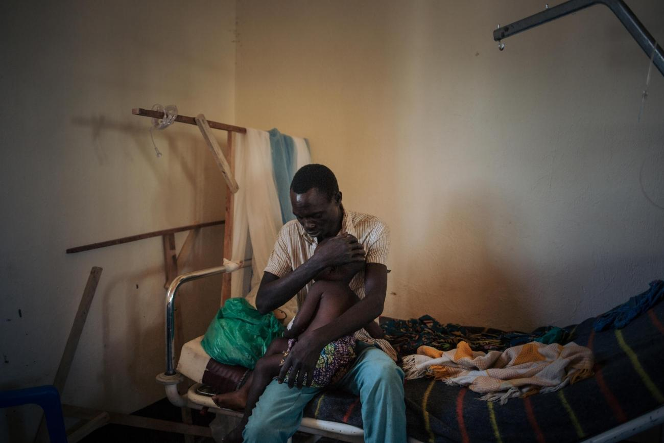 Un père tient sa fille de deux anssouffrant de la rougeole, dans l'unité de rougeole dirigée par MSF à l'hôpital de Biringi, dans la province d'Ituri, au Nord-Est de la République démocratique du Congo.  © Alexis Huguet
