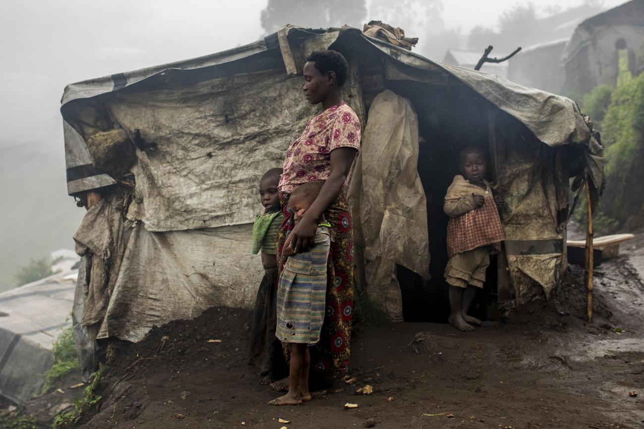 Camp de déplacés de Katale, territoire de Masisi, province du Nord-Kivu, République démocratique du Congo. Portrait d'Espérance Zawadi avec ses enfants. Elle est arrivée dans le camp il y a 2 ans et essaie de trouver de l'argent en travaillant dans les champs ou en transportant des marchandises pour 1000 francs congolais par jour (environ 50 centimes d'euros). Elle n'a reçu aucune aide au cours des 6 derniers mois et ses enfants souffrent de malnutrition : «Notre communauté a besoin de nourriture car nous n'avons plus accès à nos champs, nous avons faim», confie-t-elle. En 2019, les équipes MSF à Masisi ont constaté une augmentation importante du nombre d'enfants traités pour malnutrition.  © Pablo Garrigos/MSF