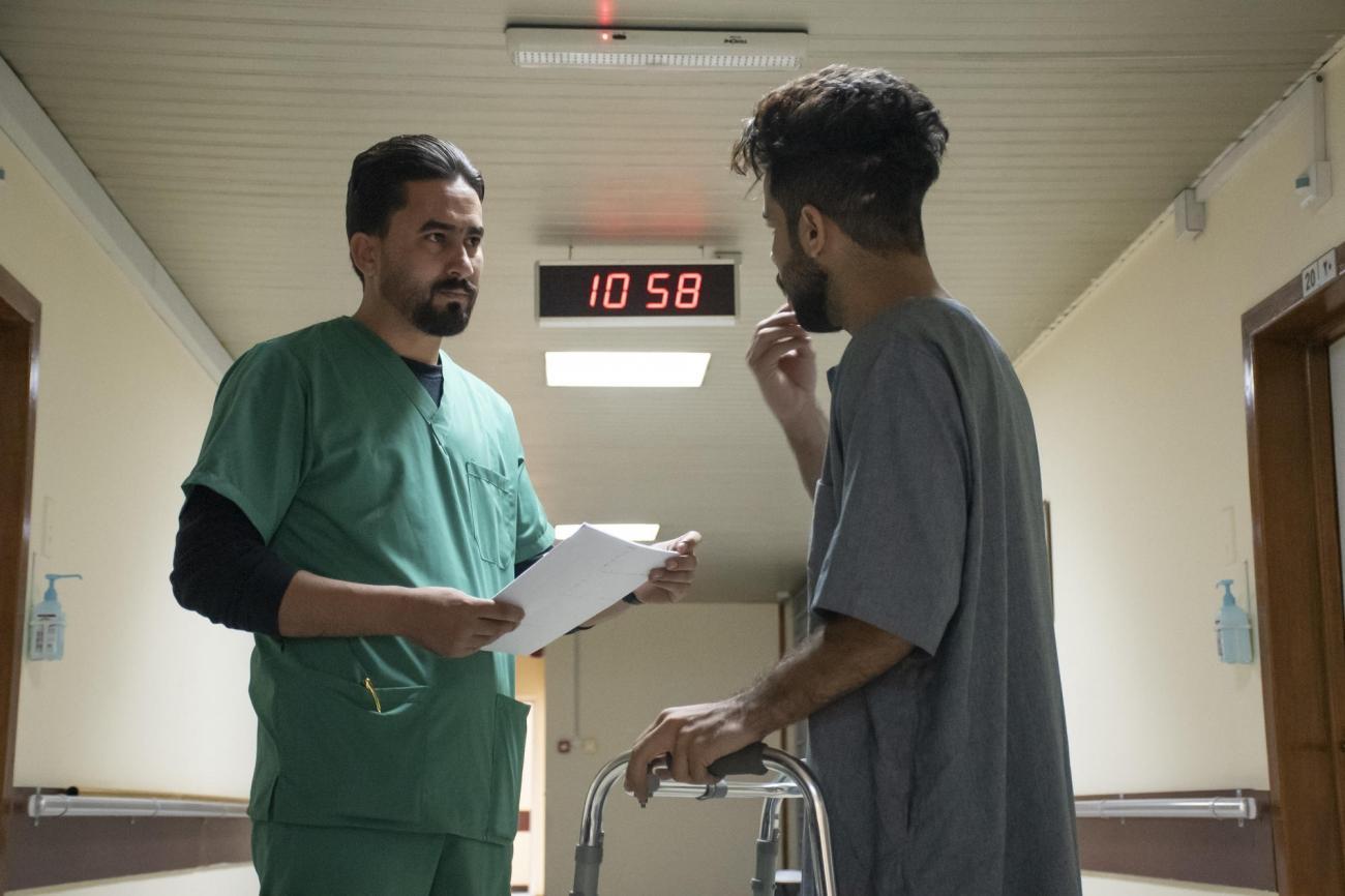 Saif parle à un membre du personnel MSF du centre de réhabilitation médicale de Bagdad. Il a été blessé lorsqu'il a été touché par une cartouche de gaz lacrymogène lors d'une manifestation à Bagdad. Ses blessures étaient si graves que sa jambe a été amputée.  © Nabil Salih/MSF
