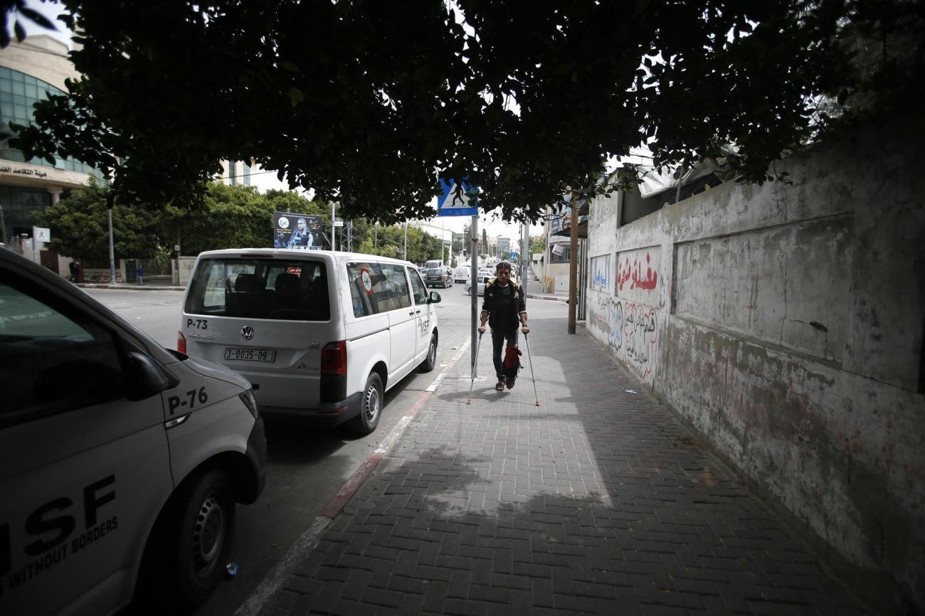 Murad, 26 ans, blessé par l'armée israélienne lors de la grande marche du retour en mai 2018, marche vers la clinique MSF de Gaza city.  © Mohammed Abed
