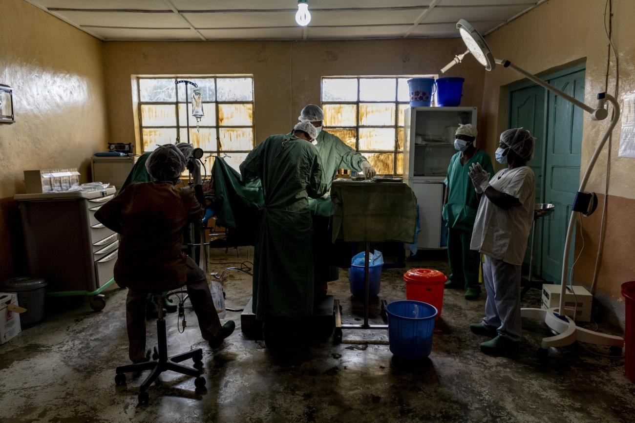 Le docteur Pacifique, directeur de l'hôpital général de Kigulube, et son équipe effectuen une césarienne, dans la pénombre.  © Pablo Garrigos/MSF