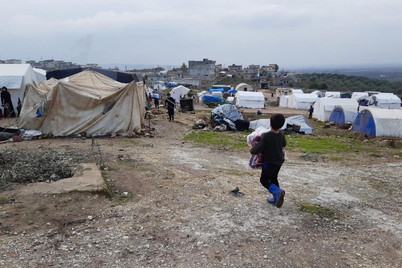 Un enfant retourne dans sa tente, portant des couvertures qu'il a reçues lors d'une distribution MSF. Le camp où lui et sa famille se sont installés, dans la région de Jebel Harem, accueille environ 120 familles.  © MSF