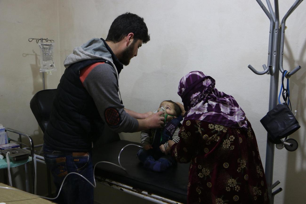 Un jeune enfant, accompagné par sa mère, se fait ausculter dans le centre de santé du camp de DeirHassan.  © Abdul Majeed Al Qareh