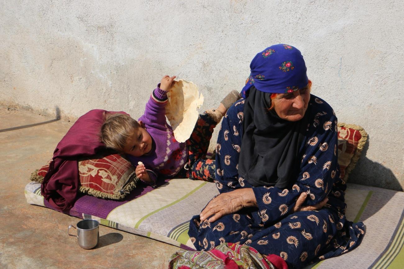 Un enfant et sa grand-mère dans le camp de Deir Hassan.  © Abdul Majeed Al Qareh