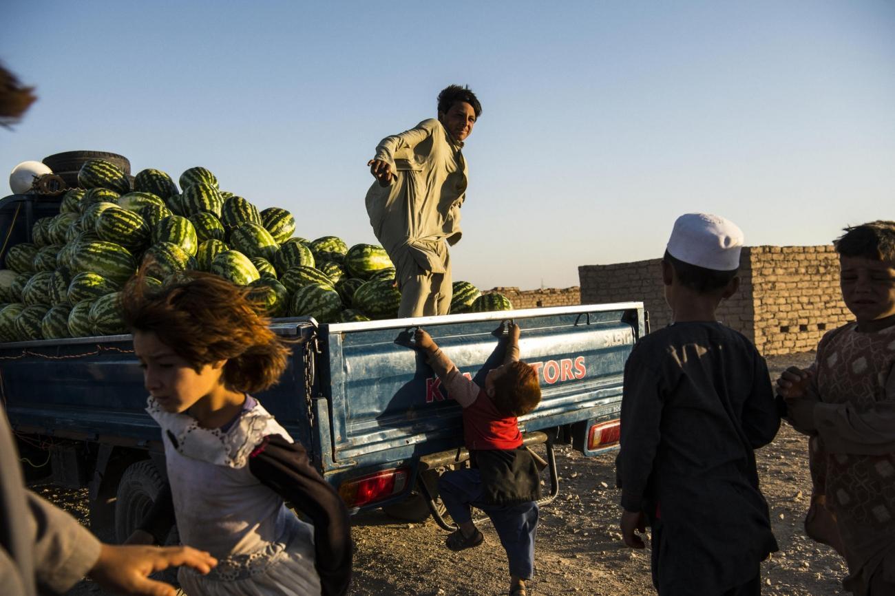 Camp de déplacés de Shahrak-é-Sabz, en périphérie de la ville d'Hérat, Afghanistan, août 2019. Des habitants viennent acheter des pastèques.  © Andrew Quilty