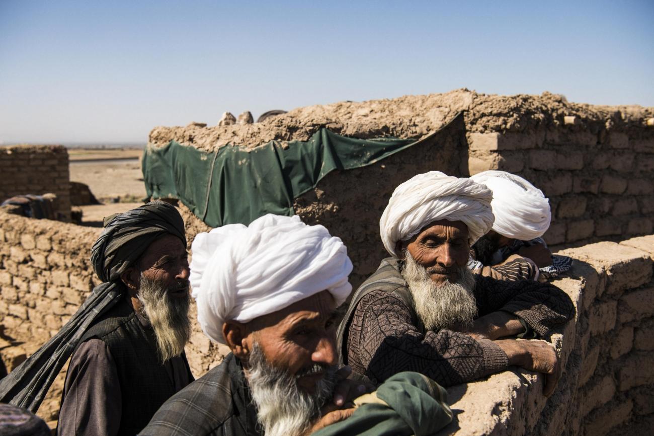 Camp de déplacés de Shahrak-é-Sabz, en périphérie de la ville d'Hérat, Afghanistan, août 2019. Des anciens se retrouvent pour observer la vie du camp.  © Andrew Quilty