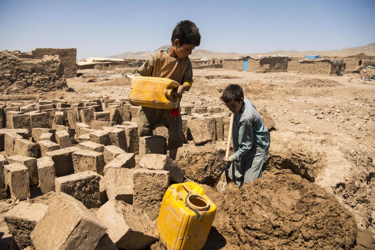 Camp de déplacés de Shahrak-é-Sabz, en périphérie de la ville d'Hérat, Afghanistan, août 2019. De jeunes garçons fabriquent des briques en terre crue.     © Andrew Quilty