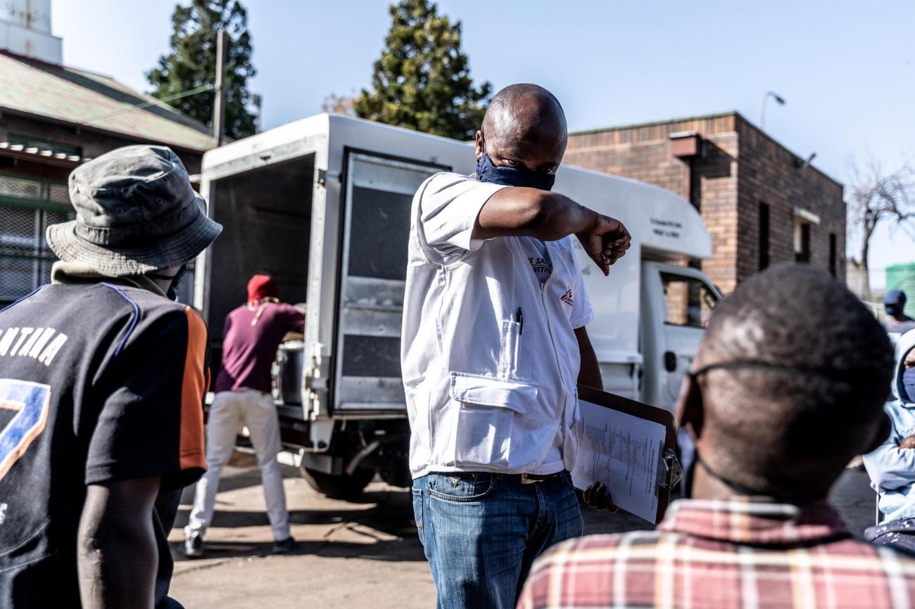 Un promoteur de la santé de MSF montre aux gens les bons gestes pour se protéger pendant la pandémie de Covid-19. Afrique du Sud.  © Tadeu Andre/MSF