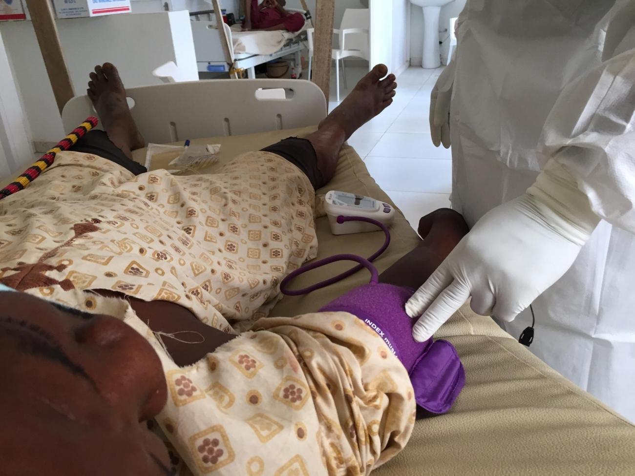Un personnel soignant prend la température d'un patient atteint du coronavirus dans l'unité Covid de l'hôpital Point G de Bamako, soutenu par MSF.  © Lamine Keita/MSF