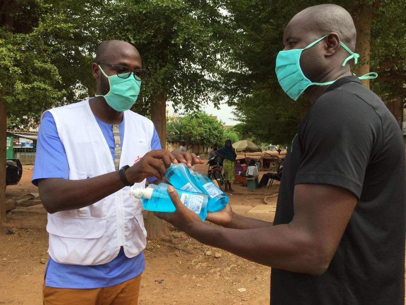 Kangni Cly, agent MSF, remet des savons liquides à un habitant pour les disposer à côté du kit de lavage de mains.  © Lamine Keita/MSF