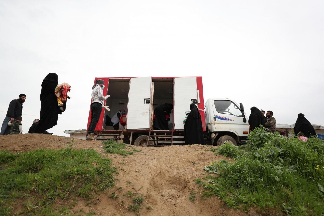 Des personnes attendent pour se faire soigner en respectant les mesures barrières de distanciation dans un camp du nord-ouest de la Syrie.  © OMAR HAJ KADOUR/MSF