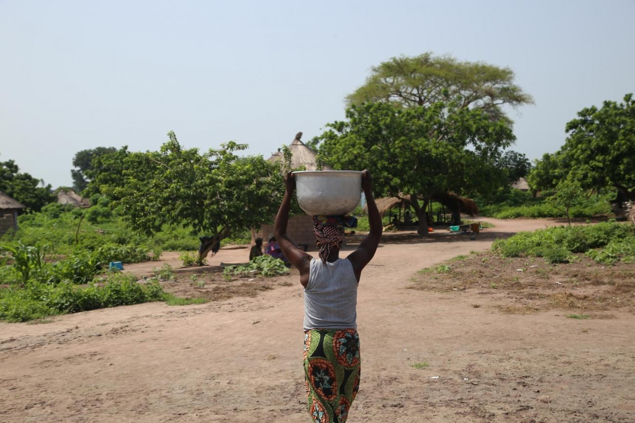 Une femme portant un seau sur la tête après l'avoir rempli à un point d'eau du site B pour les personnes déplacées de la ville de Kabo. © Igor Barbero/MSF