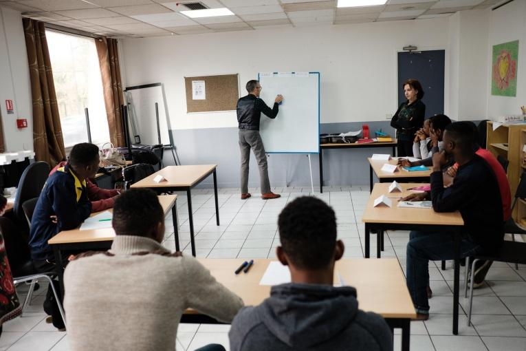 Des cours de français sont organisés par des professeurs bénévoles pour aider les jeunes à perfectionner leur niveau de langue, dans une salle d'activité de l'hôtel Passerelle de MSF. 2018. France.  © Augustin Le Gall/Haytham